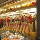 Cured meats with hanging tomatoes on vines serve dual purposes of functional decoration + actual ingredients used in cooking.